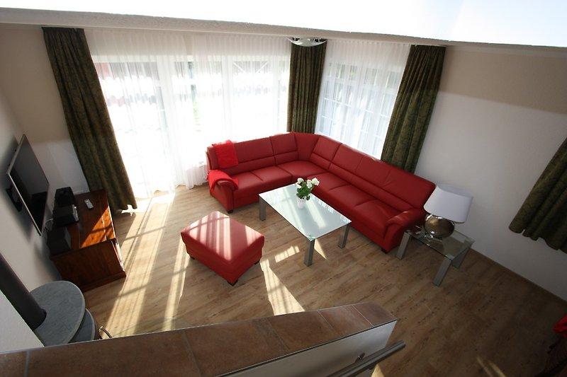 Lichtdurchfluteter Wohnraum mit Kaminofen.