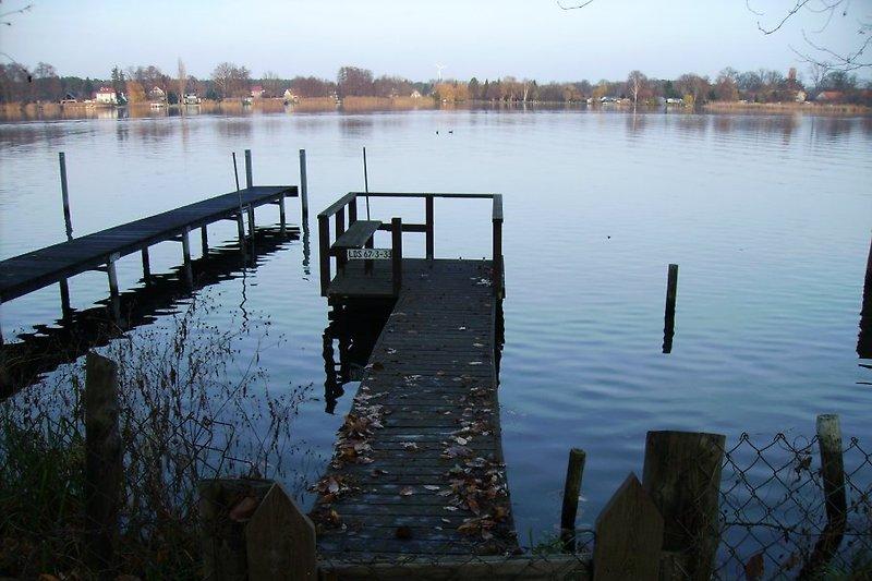Der Blick geht über den Bootssteg und weit über den See