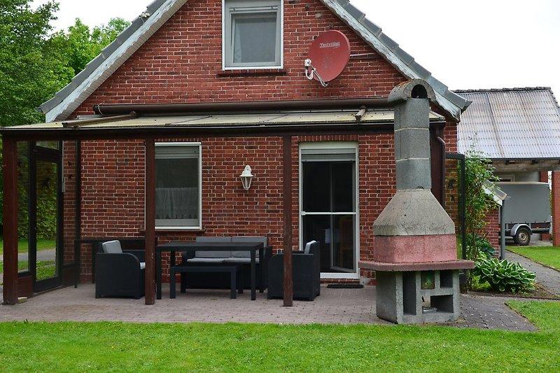 Überdachte, windgeschütze, mit Gartenmöbeln ausgestattete Südterrasse. Gartenkamin mit Grill