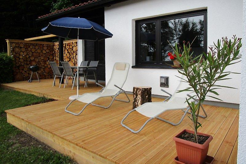 Holzterrasse mit Sitzbereich, Liegestühlen, Holzkohlegrill