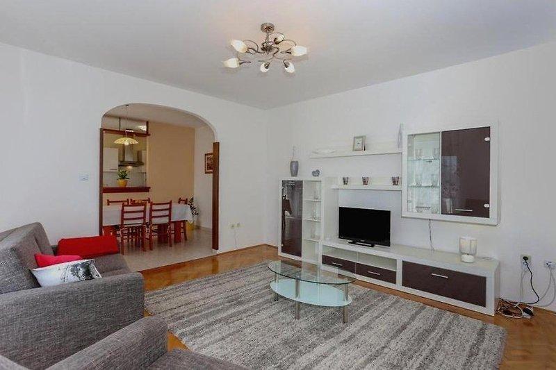 U prostranom dnevnom boravku nalaze se dvije sofe na razvlaćenje koje se koriste kao pomoćni ležajevi , sat TV, klima uređaj hlađenje/grijanje