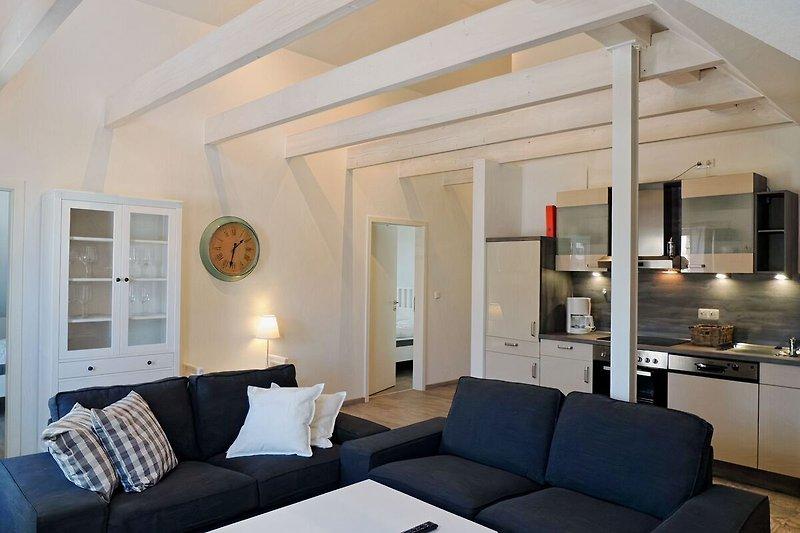 großzügige Couch-Garnitur mit Küche im Hintergrund