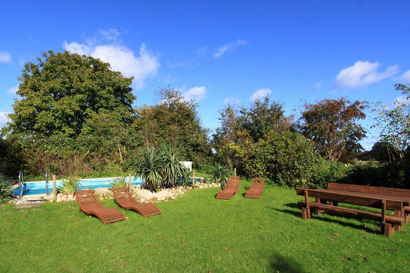 Swimmingpool mit Sonnenliegen und Tisch, Stühlen, Grill und Gartenlaube