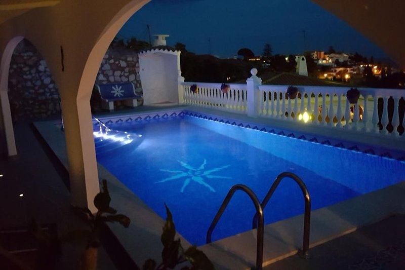 nachts beleuchteter Pool mit Ausblick über die City und das Meer