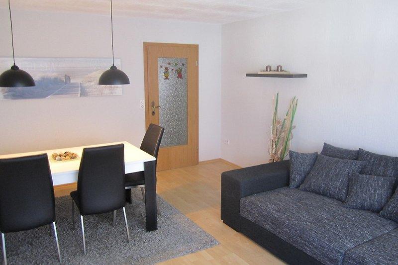 Wohnzimmer mit großem Sofa und Tisch für sechs Personen (drei Stühle, eine Sitzbank)