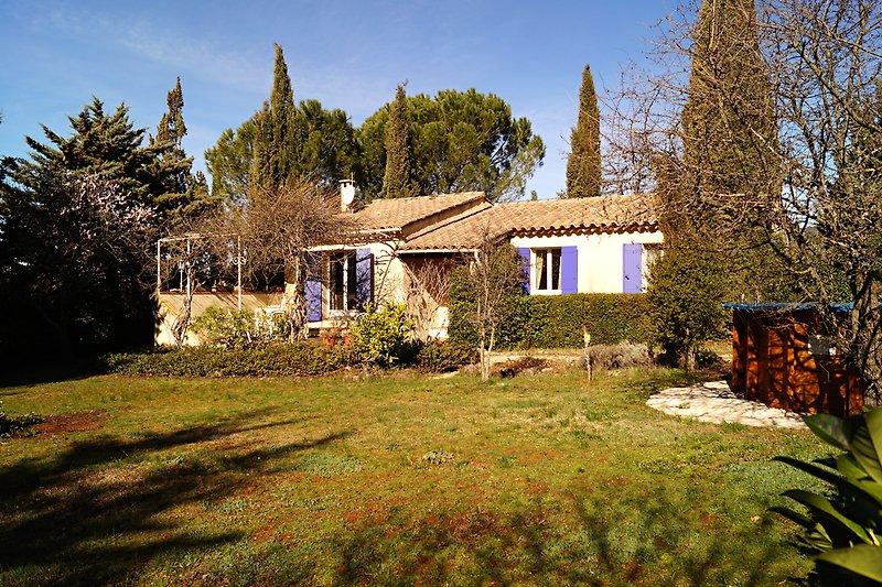 Blick aufs Haus mit Terrasse (links) und Pool (rechts), vom Garten (Rasenfläche), im Spätwinter.
