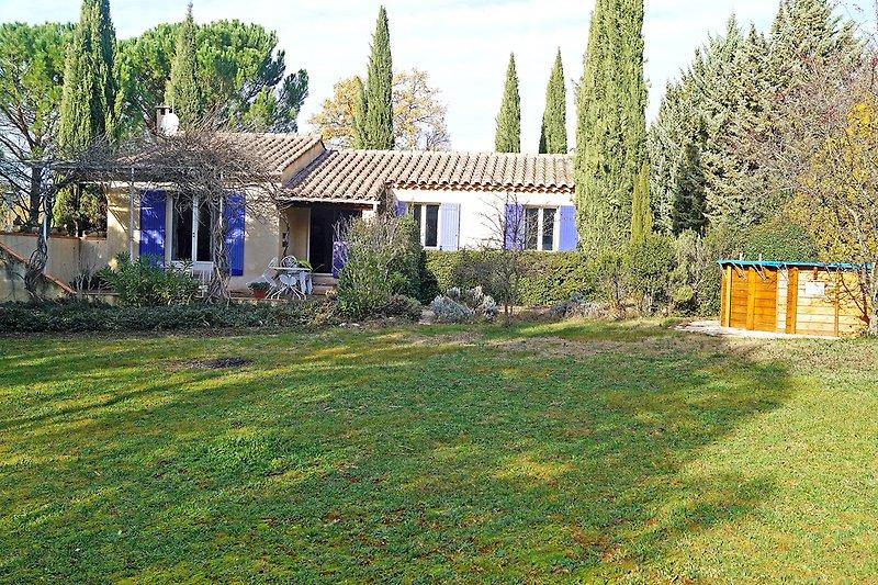 Rasenfläche des Gartens, Haus mit Terrasse und Pool im Herbst (am späten Nachmittag).