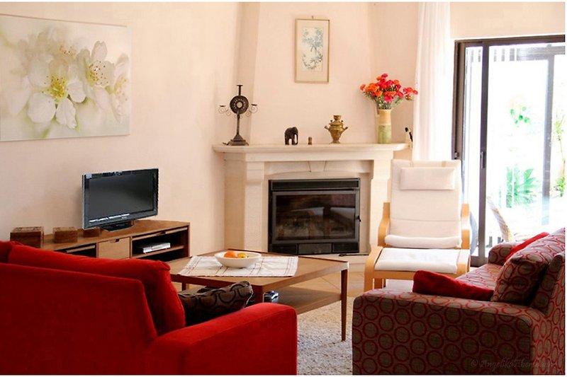 Wohnbereich mit Flach-TV und Kamin, große Schiebetür zum Garten