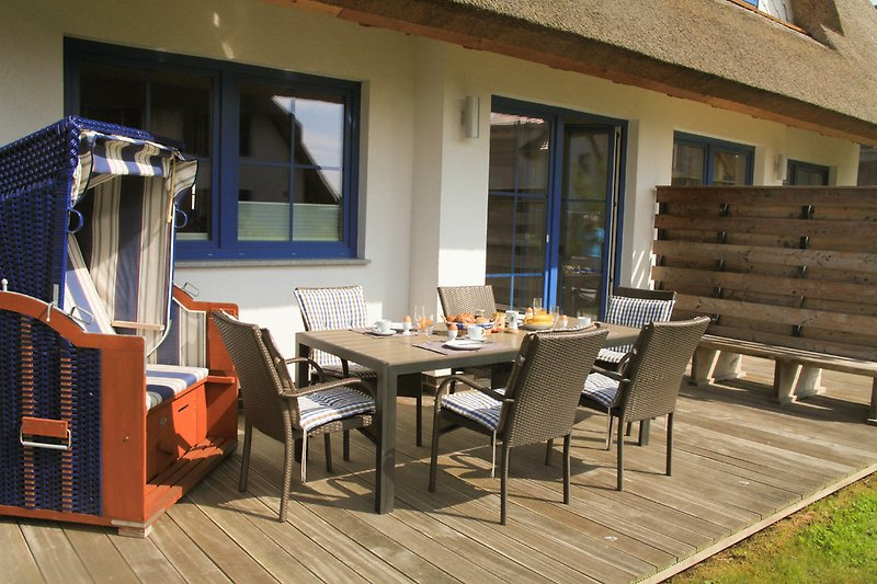 Holzterrasse mit Terrassenmöbeln und Strandkorb