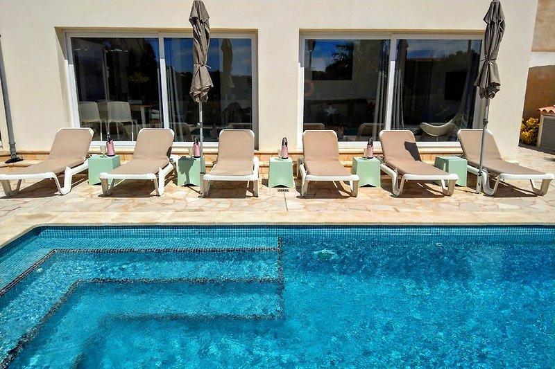 Poolbereich mit Sonnenliegen und Schirmen
