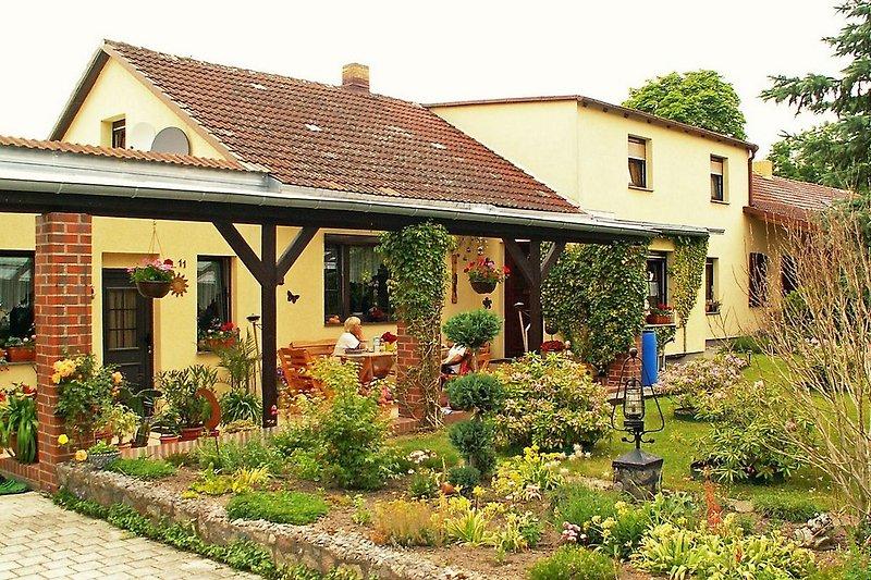 Überdachte Terrasse und zwei Fenster der Ferienwohnung rechts oben