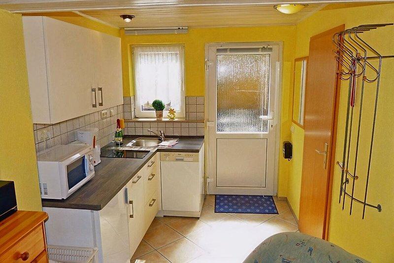 Küchenzeile mit Geschirrspüler und Garderobe am Eingang