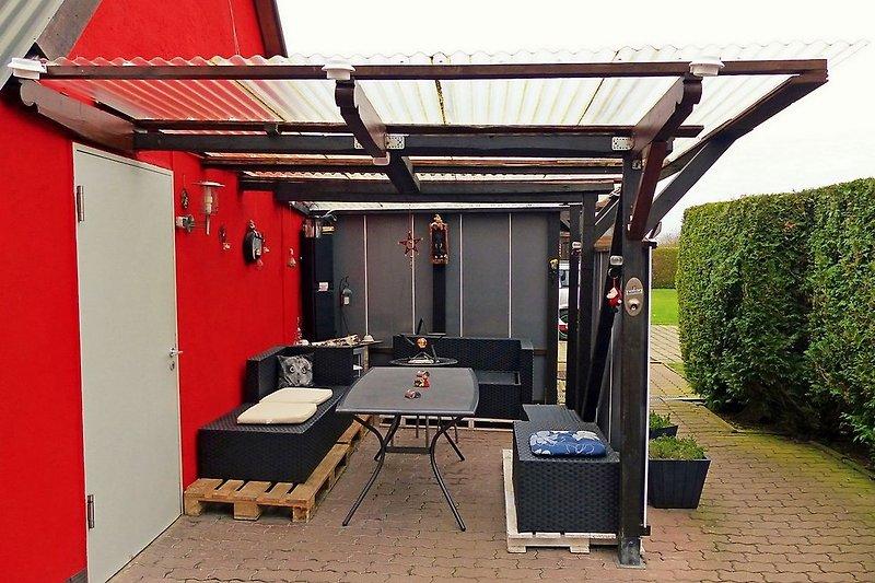 Überdachte Terrasse - im Hintergrund die Spiel-und Liegewiese
