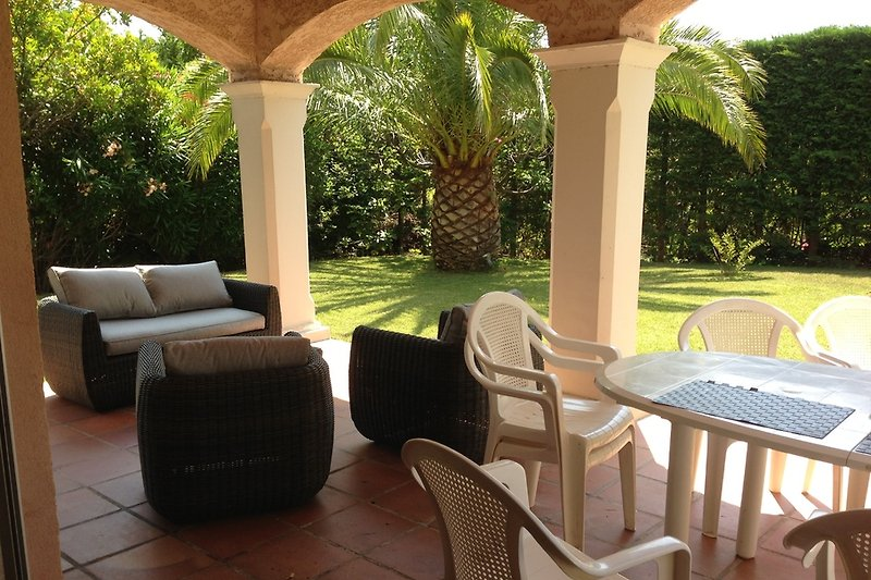 überdachte Terrasse zum Garten mit Esstisch und Wohnecke