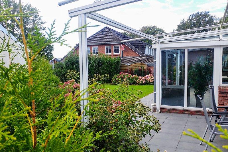 sonnige Terrasse mit sichtgeschütztem Garten