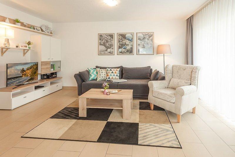 Wohnbereich mit gemütlichem Ohrensessel und bequemem Sofa mit Schlaffunktion.