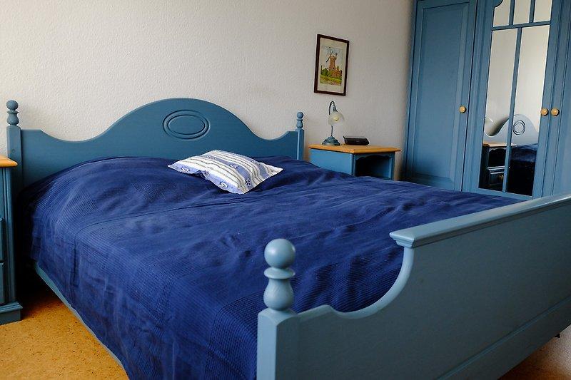 Schlafzimmer mit Doppelbett und großzügigem Kleiderschrank