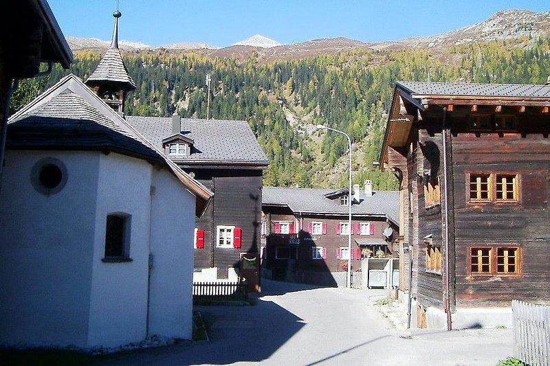 Dorfstrasse Oberwald mit Haus und Kapelle