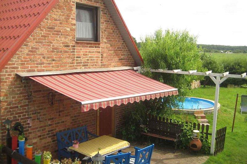 Ansicht vom FerienHaus mit Terrasse und Pool im Garten