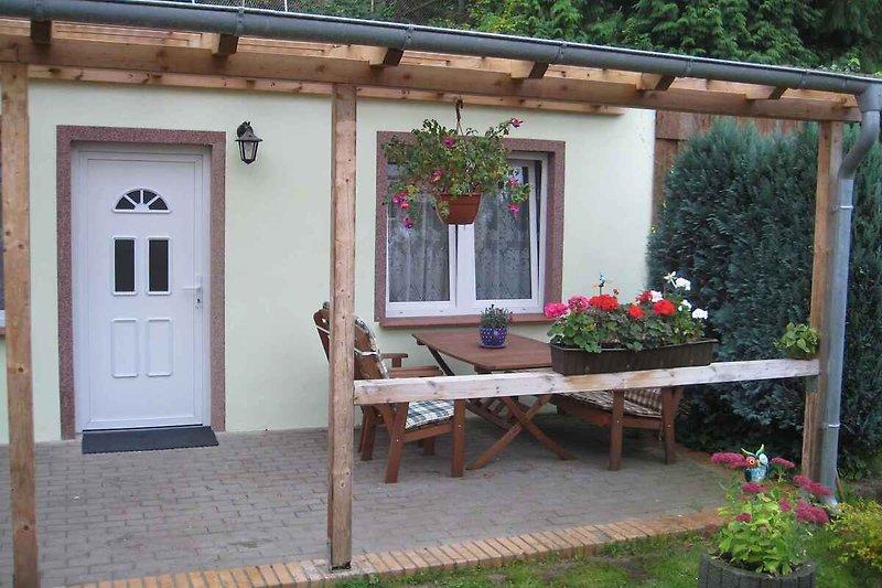 Aussenansicht mit Eingang in die Ferienwohnung mit überdachter Terrasse