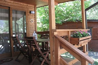 Wooden CHALET of 39 square meters consisting of 2 double bedrooms, a bathroom with shower, a living room with kitchen, dining room, table and chairs.