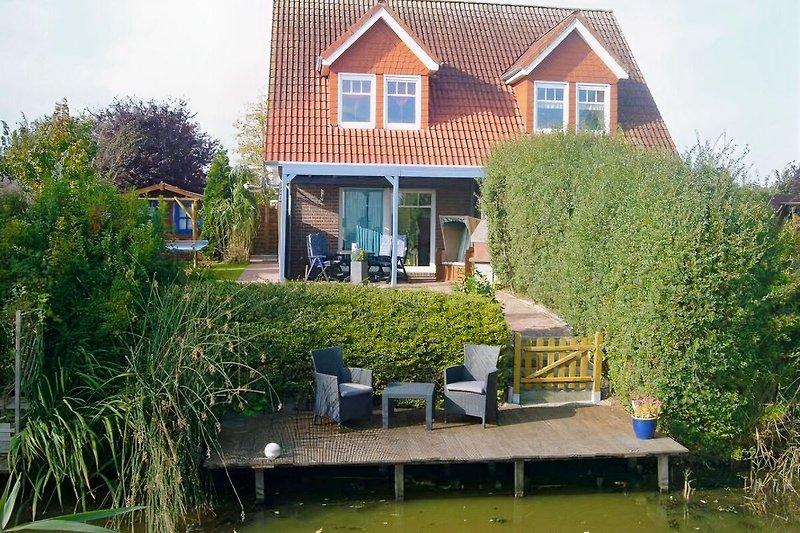 Blick auf den eigenen Bootssteg und der tollen, überdachten Terrasse mit Strandkorb und Gartengrill.