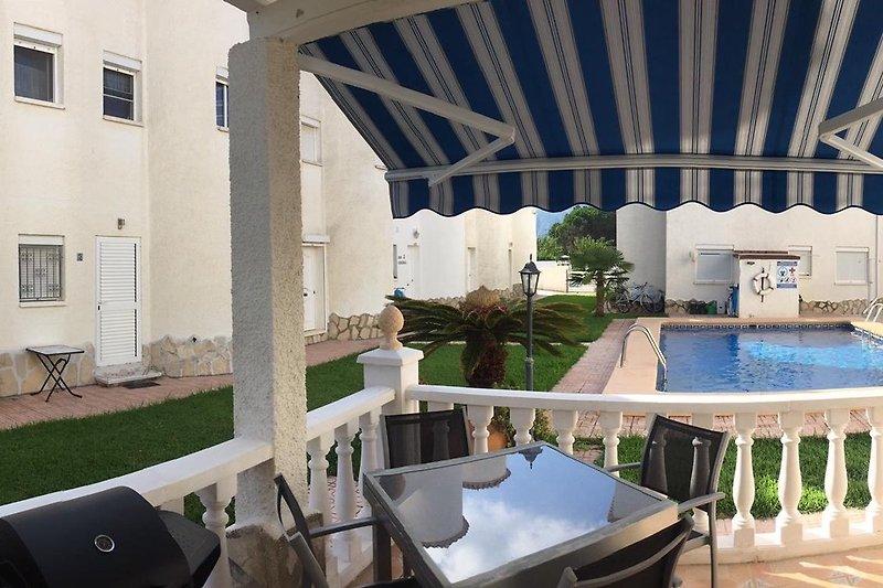 Terrasse am Pool mit Gasgrillecke und großer Markise