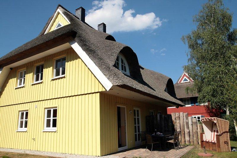 Haus mit sonniger Terrasse, Wiese und Strandkorb