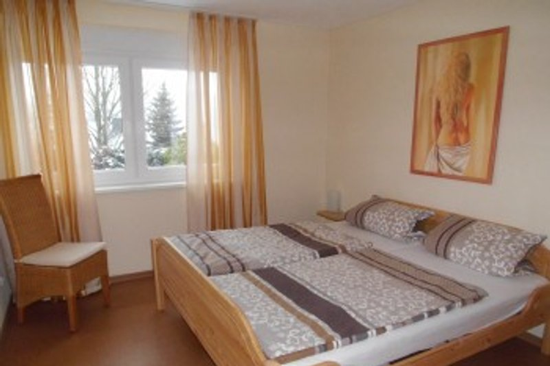 Das große Schlafzimmer ist mit einem Doppelbett sowie einem großen Schrank ausgestattet. Auch hier sorgt die Fußbodenheizung für ein angenehmes Raumklima