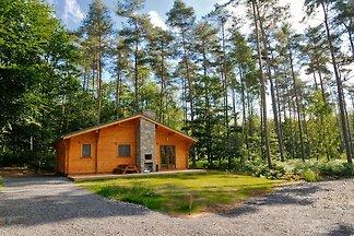 Modernes Holzchalet im Wald, mit Holzofen