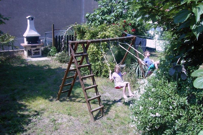 Garten mit Grill und Schaukel.