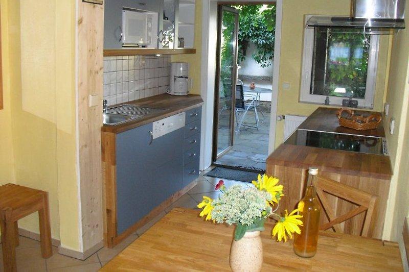 Küche mit Blick auf den Grillplatz mit Kamin und die Frühstücksterrasse