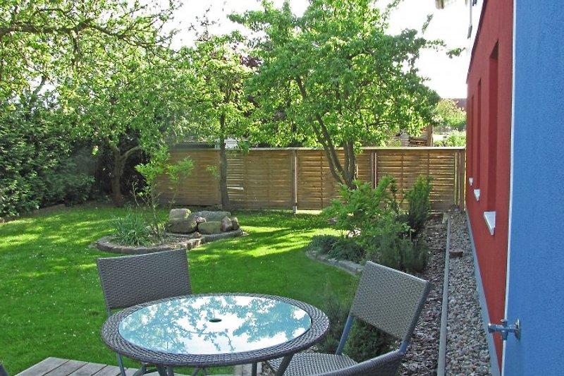 eingezäunter Garten mit großer Terasse, 2 Liegen und Holzkohle-Grill