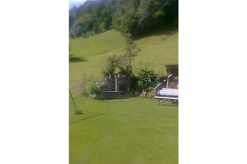 Zum Haus gehört ein Garten mit Sitzgruppe und Gartengrill.