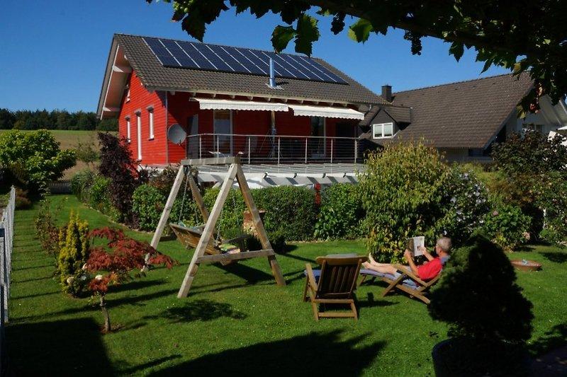 Blick aus der Weinlaube durch den Garten auf das Schwedenhaus