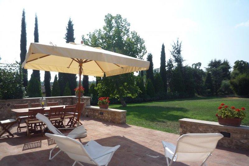 Die Terrasse mit Esstisch und Liegestühle, im Hintergrund der Garten.