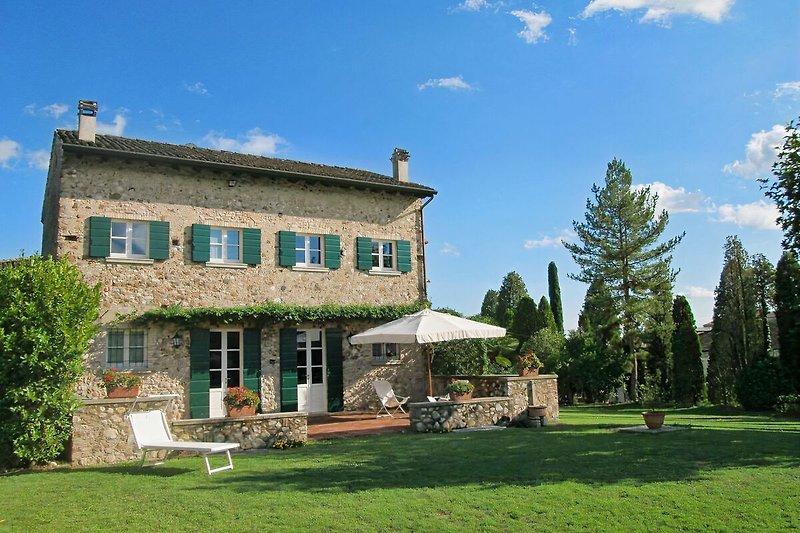 Das Ferienhaus Lucertola mit der Terrasse vom Garten gesehen, in September..