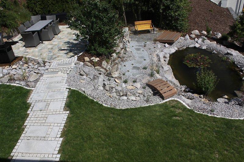 Blick in den Garten mit Teich, Grill, Feuerstelle und Sitzmöglichkeit