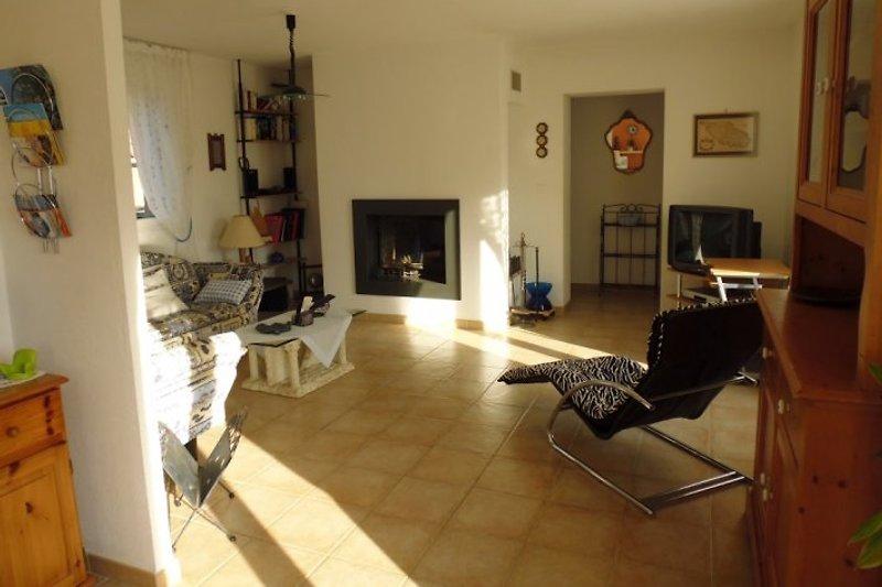 Gemütliches Wohnzimmer mit Cheminée, TV, kleine Bibliothek
