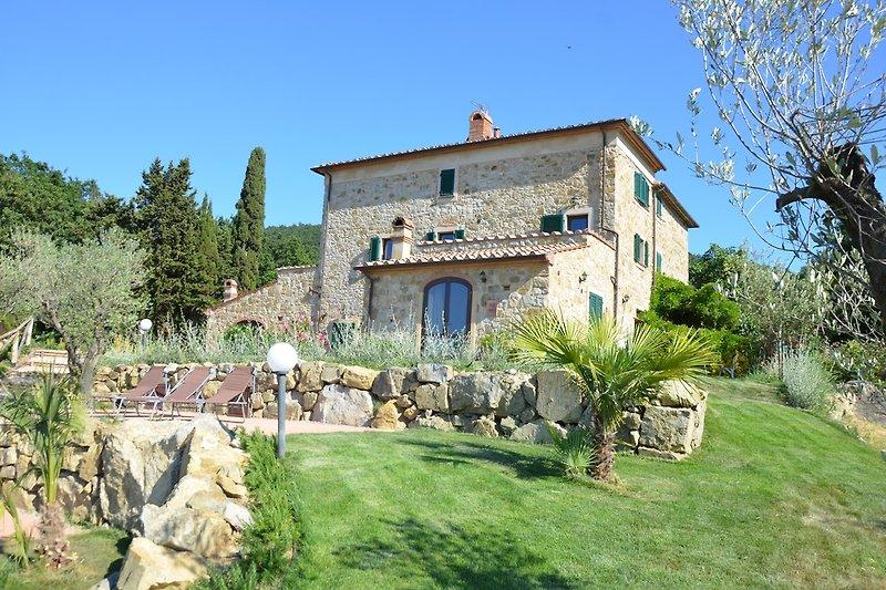 Helles Wiesen-Grün, terrassenförmige Natursteinmauern, Zypressen, Palmen und Olivenbäume umsäumen das Landhaus