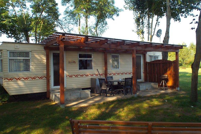 Mobilheim mit überdachter Terrasse, Grill und Sitzgruppe
