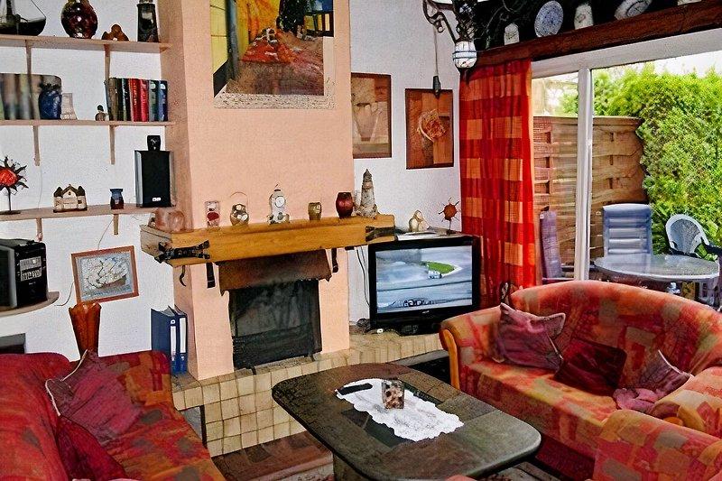 Wohnzimmer mit offenem Kamin und wunderschönem weiten Panoramblick ins Grüne!