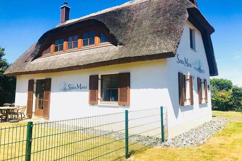Zum Haus gehört ein großes eingezäuntes Grundstück mit sonniger Terrasse