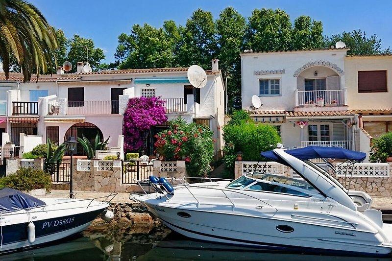 Ferienhaus und Bootssteg vom Kanal aus