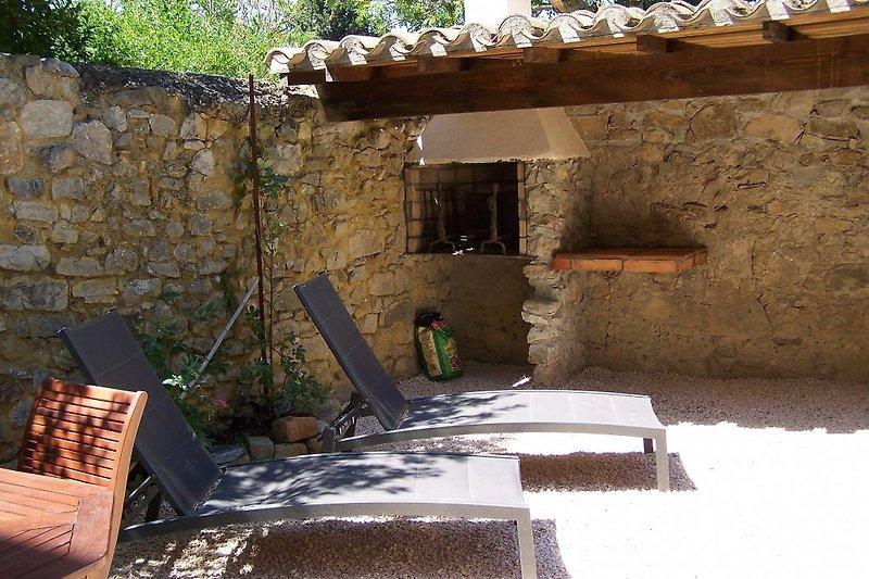 Terrasse, geschützt von Mauern, mit Liegen und Barbecue
