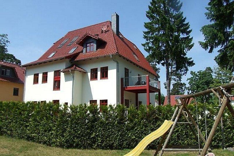 Das Haus vom Garten aus gesehen, mit Rutsche und Schaukel