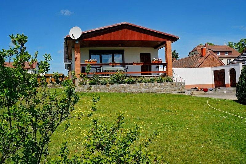 Vorderansicht des Hauses mit der überdachten Terrasse und großer Rasenfläche