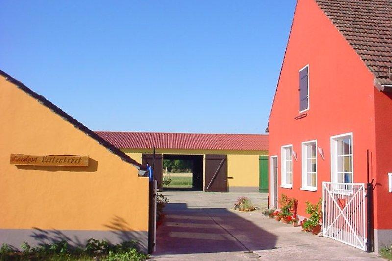 Ferienhaus in orange. Hof mit Scheune. Dahinter der große Garten.